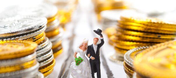 Brautpaar-Figur zwischen Geldmünzen