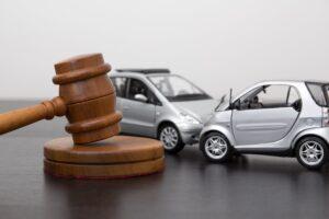 Modellautos mit Unfall hinter einem Richterhammer