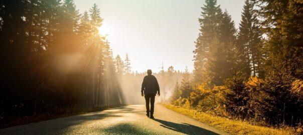 Mann läuft auf der Straße bei Sonnenaufgang