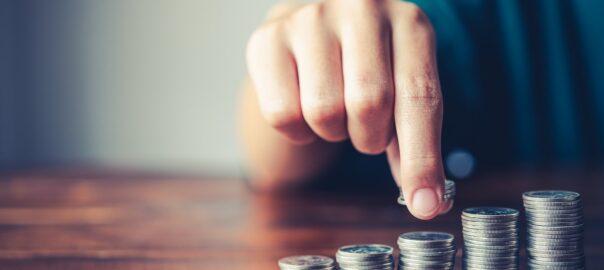 Mann stapelt Münzen vor sich auf dem Tisch