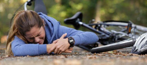 Frau liegt nach Fahrradsturz am Boden