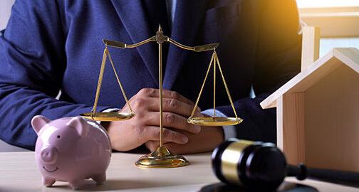 Anwalt, der vor einer Waage, einem Richterhammer, einem Sparschwein und einem Modellhaus sitzt