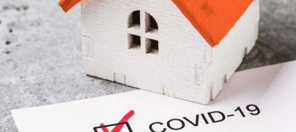 Haus, das auf einem Dokument it der Aufschrift Covid-19 liegt