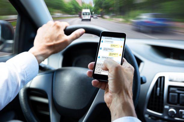 Autofahrer hält ein Handy in der Hand