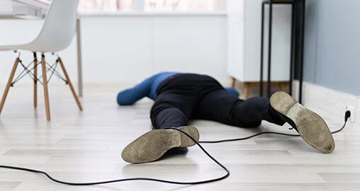 Mann liegt am Boden nach Sturz über ein Kabel