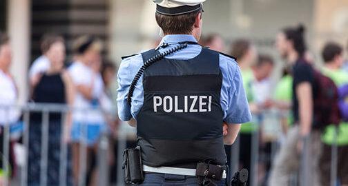 Polizist steht mit dem Rücken zur Kamera