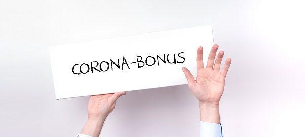 Mann hält Schild mit Aufschrift Corona-Bonus