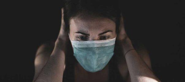 Frau mit Mundschutz, in einer nachdenklichen Pose - Arbeitsrecht.